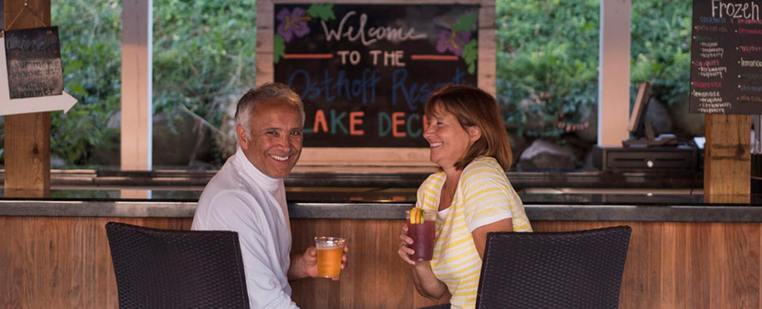 A couple enjoys drinks at Osthoff Lake Deck