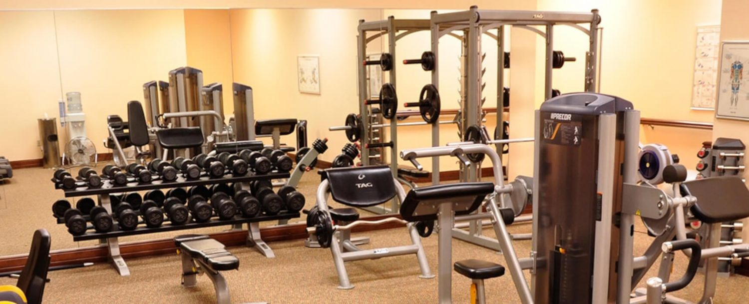 A workout room with free weights and machines.