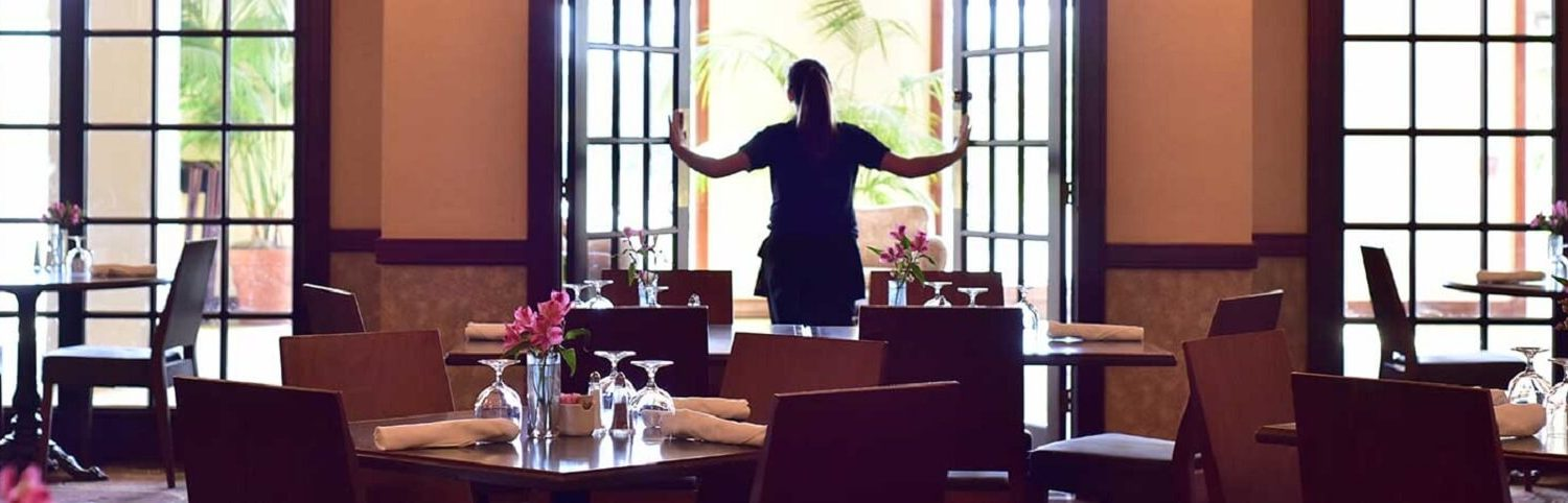 employee opening french doors at Otto's Restaurant