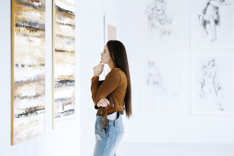 Woman observing a painting at an Elkhart Lake art gallery